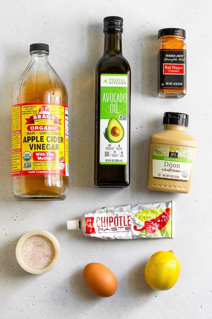 White counter top with a jar of avocado oil, cayenne pepper, dijon mustard, chipotle paste, lemon, egg, salt, and apple cider vinegar.