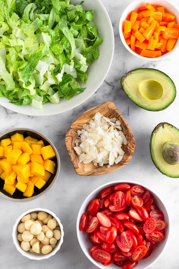 White counter with a big bowl of chopped lettuce, bowl of peppers, an avocado cut open, bowl of halved tomatoes, bowl of macadamia nuts, bowl of diced mango, and a plate of coconut flakes.