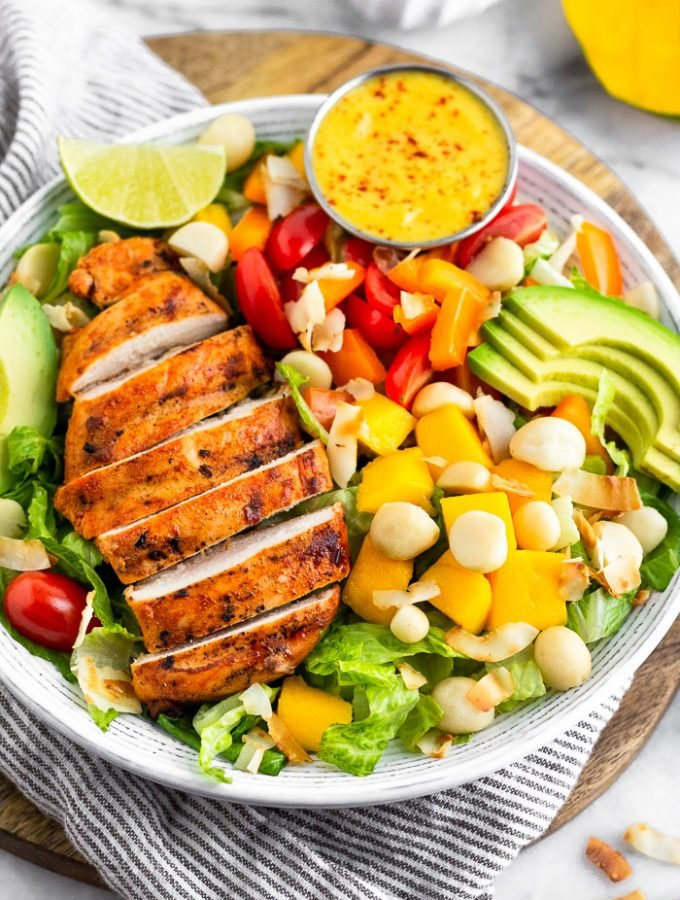Large bowl of tropical chicken salad with grilled chicken, mango, macadamia nuts, avocado, tomatoes, peppers, and coconut flakes on a bed of lettuce. It is sitting on stripped towel on a circular cutting board with a mango behind it.
