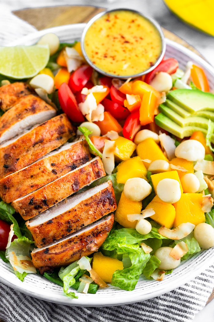 Close up of a large bowl of tropical chicken salad with grilled chicken, mangos, coconut, avocado, tomatoes, peppers, and shredded coconut. There is a small ramekin of coconut mango dressing in the bowl. A mango is behind the bowl.