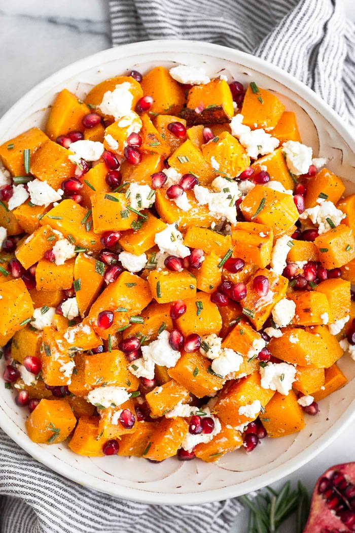 Bowl filled with roasted butternut squash, goat cheese, pomegranates, and rosemary all mixed together. It is sitting on a kitchen towel with half a pomegranate and more rosemary next to it.