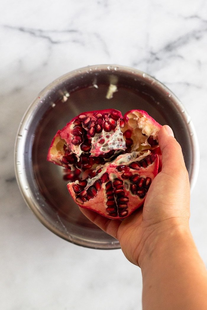 A hand holding half a cut pomegranate over a bowl filled with water