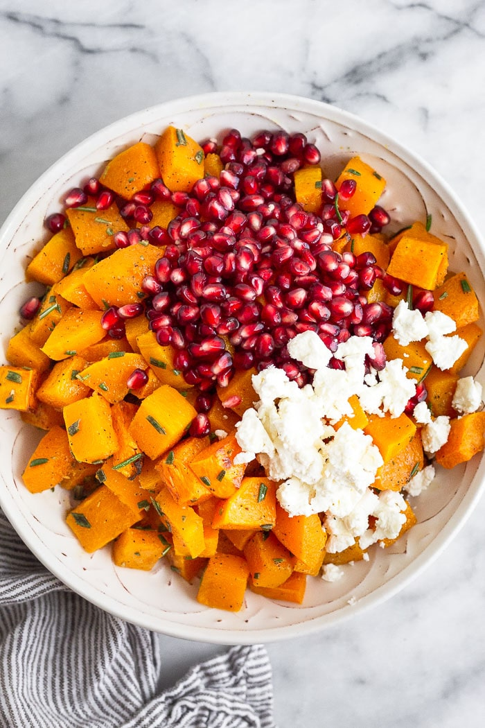 Overhead shot of a large bowl filled with roasted cubed butternut squash, pomegranates, and goat cheese.