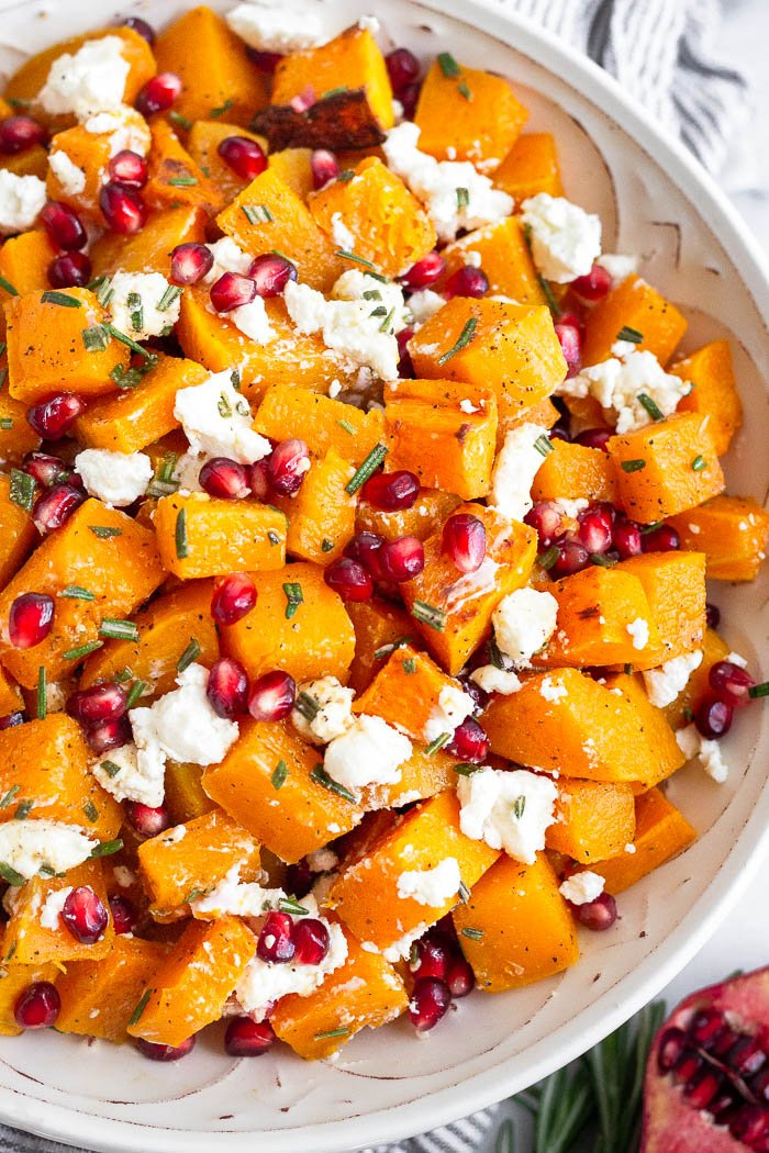 Bowl filled with roasted butternut squash, goat cheese, pomegranates, and rosemary all mixed together.