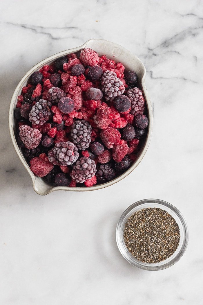 Bowl of mixed frozen berries and a small bowl of chia seeds on a white counter top.
