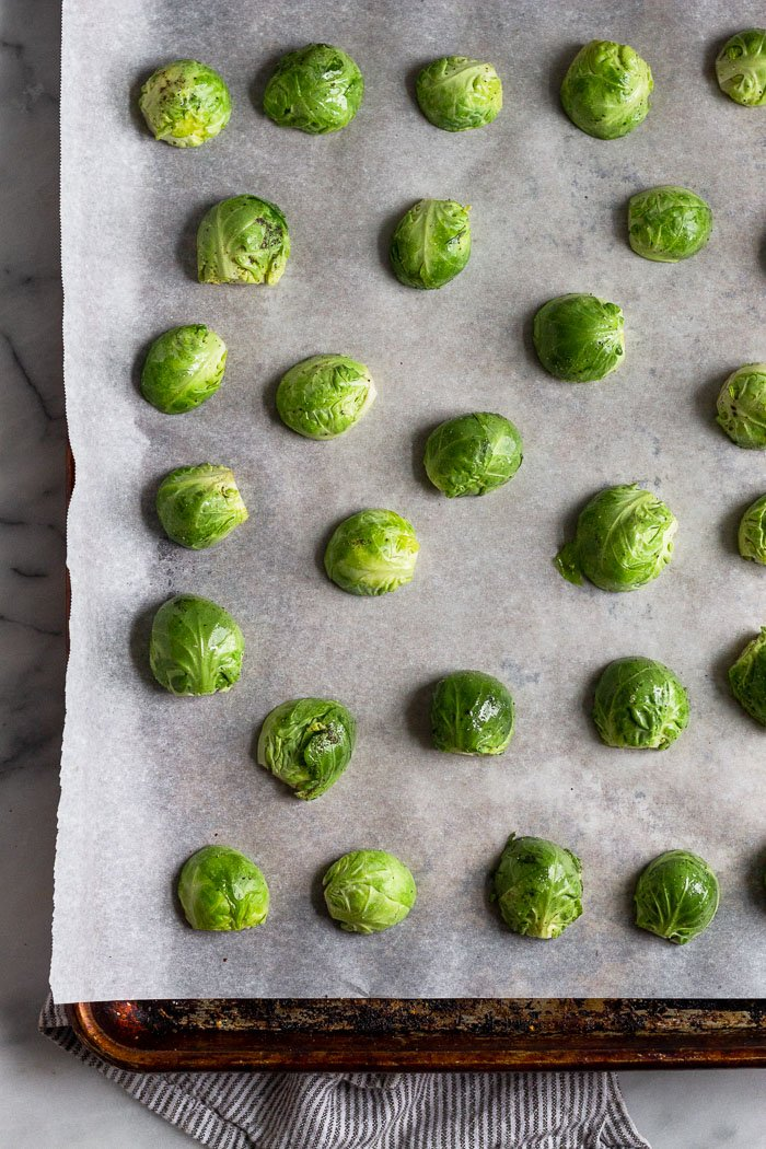 Baking sheet lined with parchment paper with halved brussel sprouts facing cut side down.