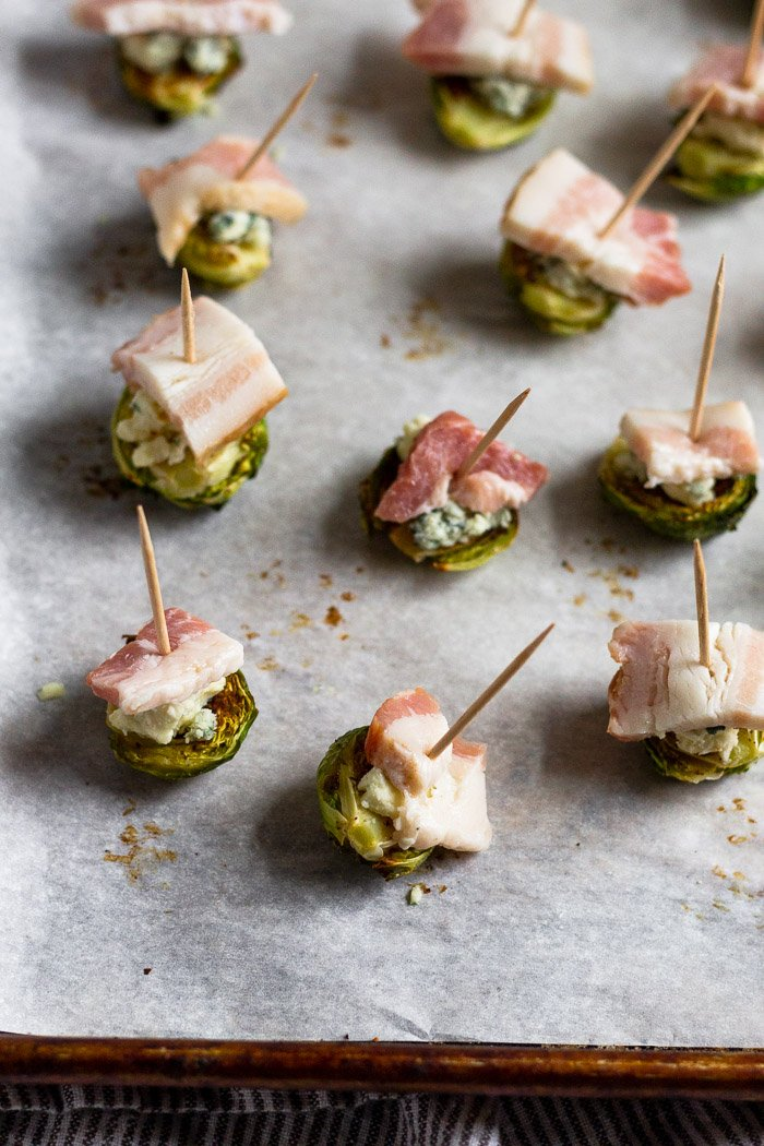 Individual roasted Brussel sprouts topped with blue cheese and a piece of raw bacon on a baking sheet. A toothpick is stuck in each of them.