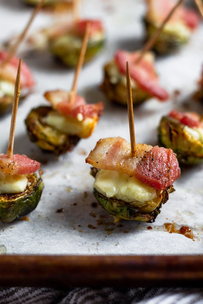 A bunch of halved brussel sprouts that have been roasted and topped with blue cheese and crispy bacon. A toothpick is stuck in each one.