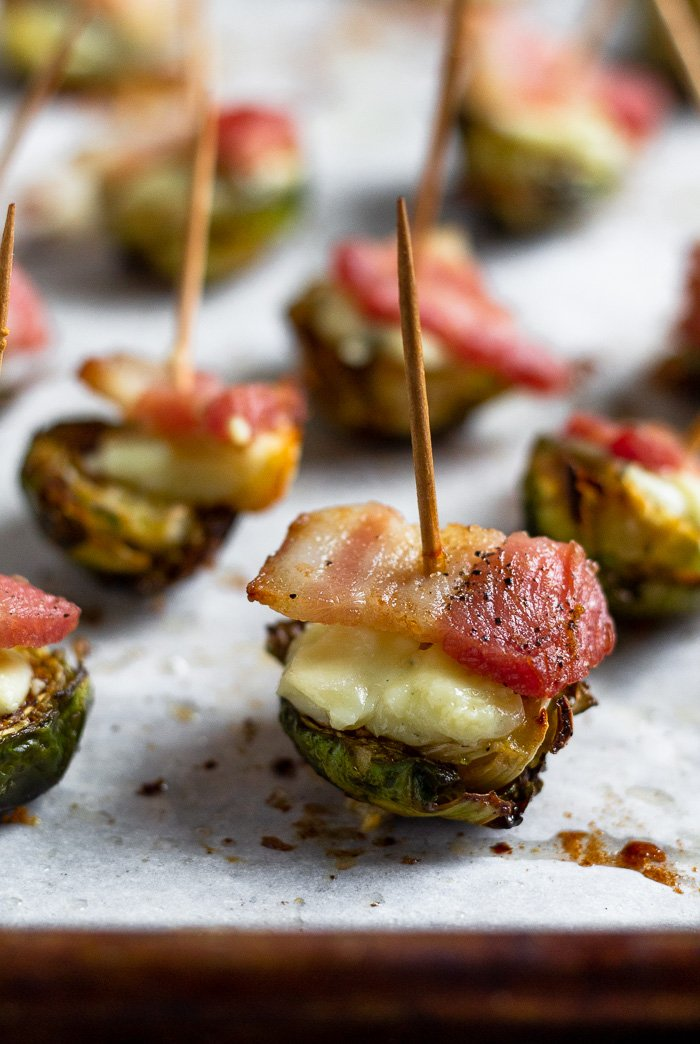 Individual halved roasted brussel sprouts topped with blue cheese and bacon with a toothpick stuck in them.