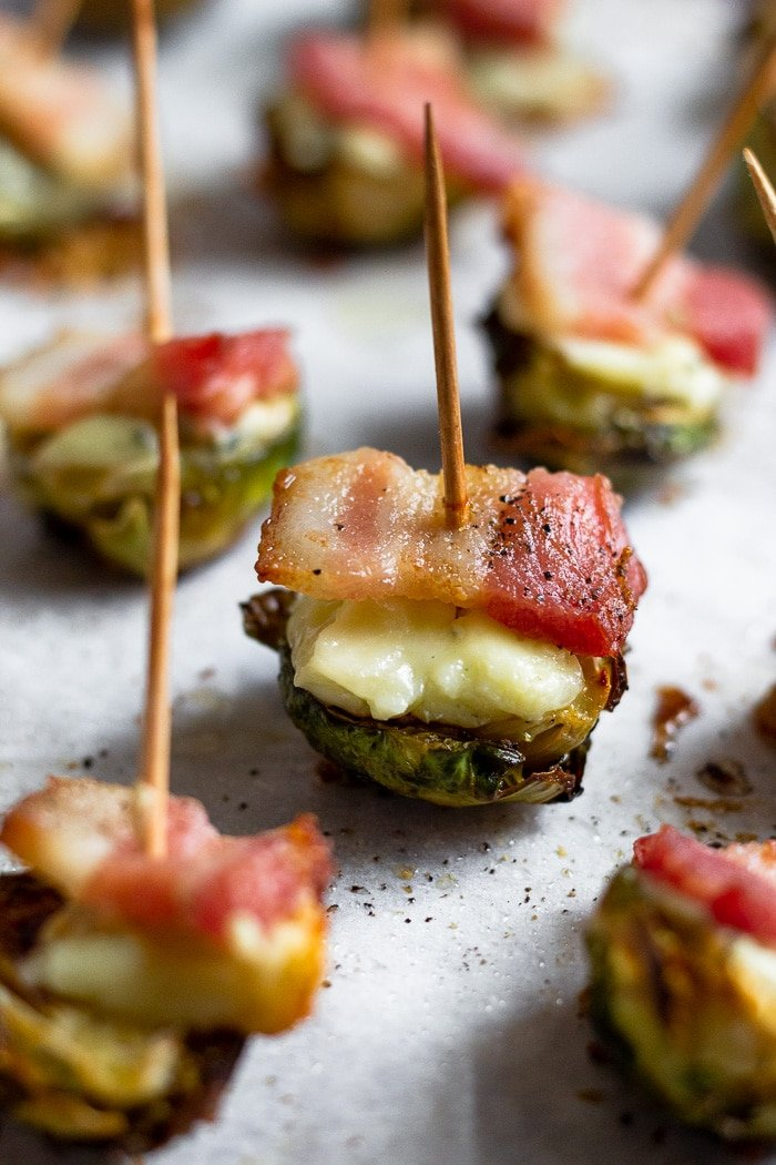 Individual crispy brussel sprouts with bacon and cheese with a toothpick stuck in each one.