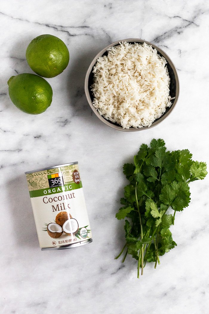 A can of full fat coconut milk. 2 limes, bowl of uncooked white rice, and a small bunch of cilantro on a white counter top to make coconut cilantro lime rice.