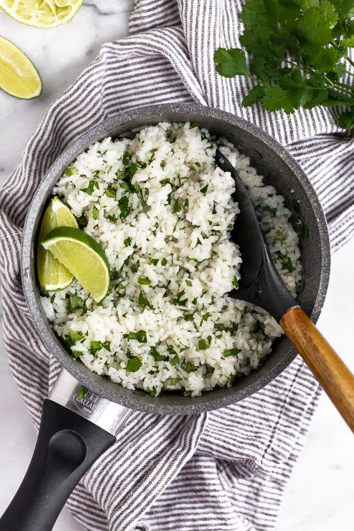Small sauce pan filled with coconut cilantro lime rice garnished with lime wedges. Around it is more limes and cilantro.