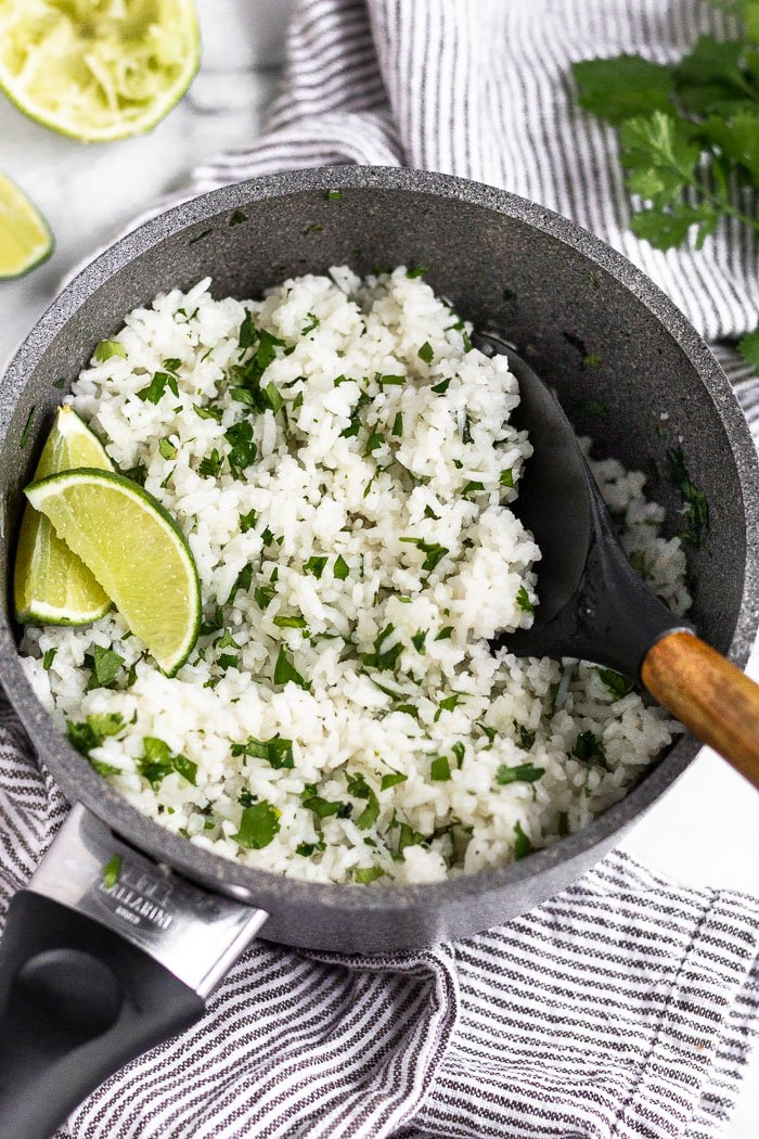 A small pot filled with cooked coconut cilantro lime rice garnished with lime wedges. The pot is sitting on a stripped towel and around it is more limes and cilantro.