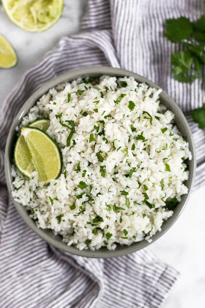 A bowl filled with coconut cilantro lime rice garnished with two lime wedges and surrounded by more limes and cilantro.
