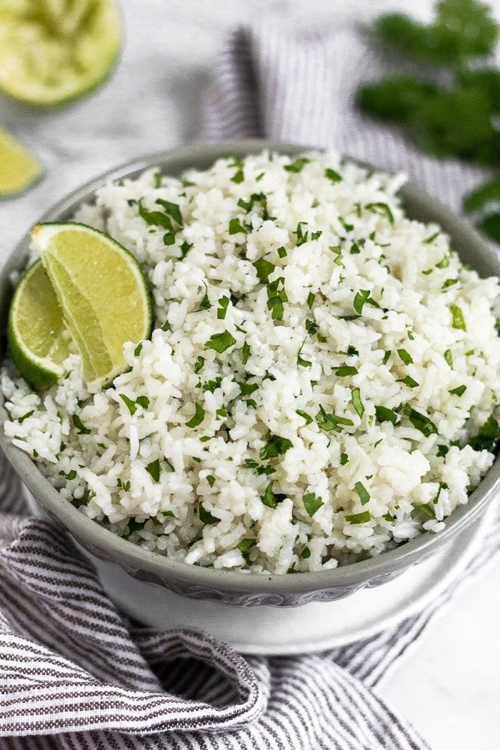 Coconut cilantro lime rice in a grey bowl garnished with lime wedge. The bowl is sitting on a small white plate on a towel with limes and cilantro behind it.