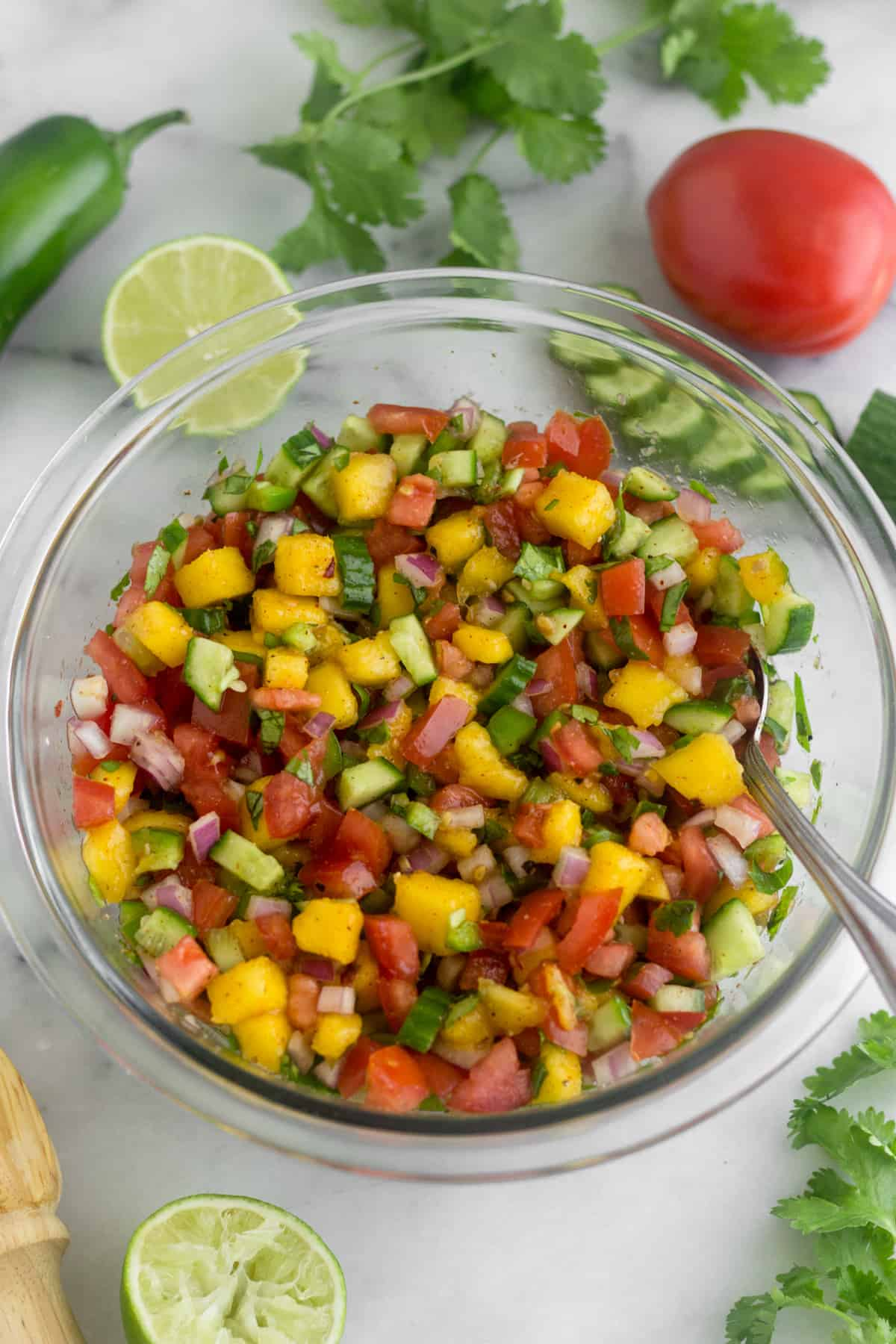 Large glass bowl filled with Mango Cucumber Salsa with a spoon coming out of it