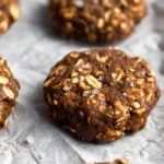 Healthy chocolate peanut butter no bake protein cookies on a parchment paper sprinkled with sea salt.