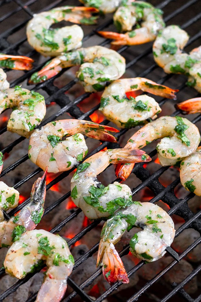 Raw shrimp on skewers on a grill.