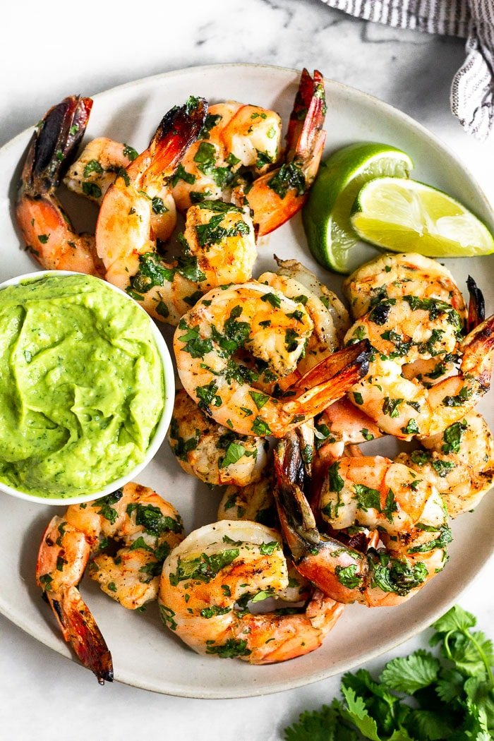 Plate of grilled cilantro lime shrimp with a small dish of avocado sauce and lime wedges. A bunch of cilantro and a kitchen towel is around it.