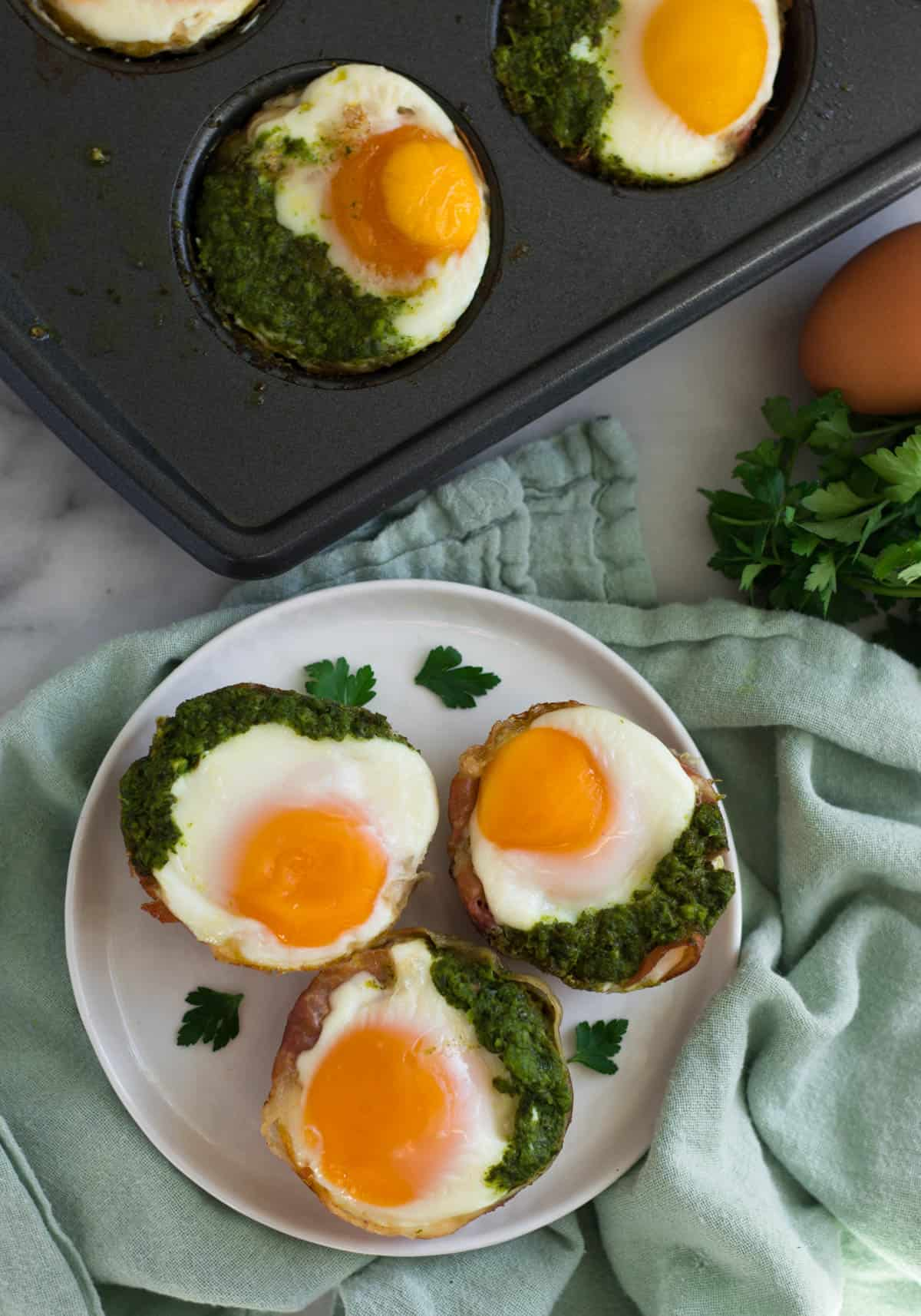 Overhead of 3 prosciutto egg cups on a white plate and a muffin tin with more egg cups