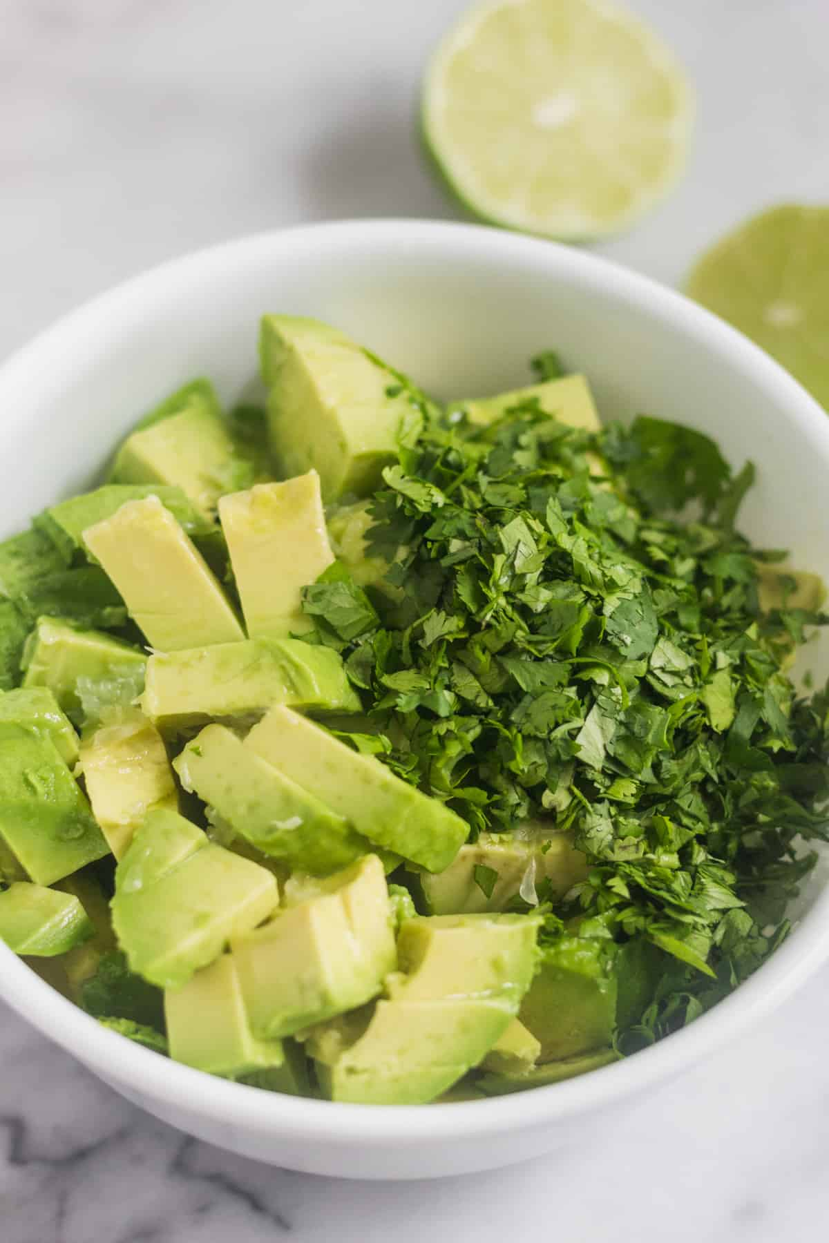 White bowl filled with diced avocado, lime juice, and chopped cilantro