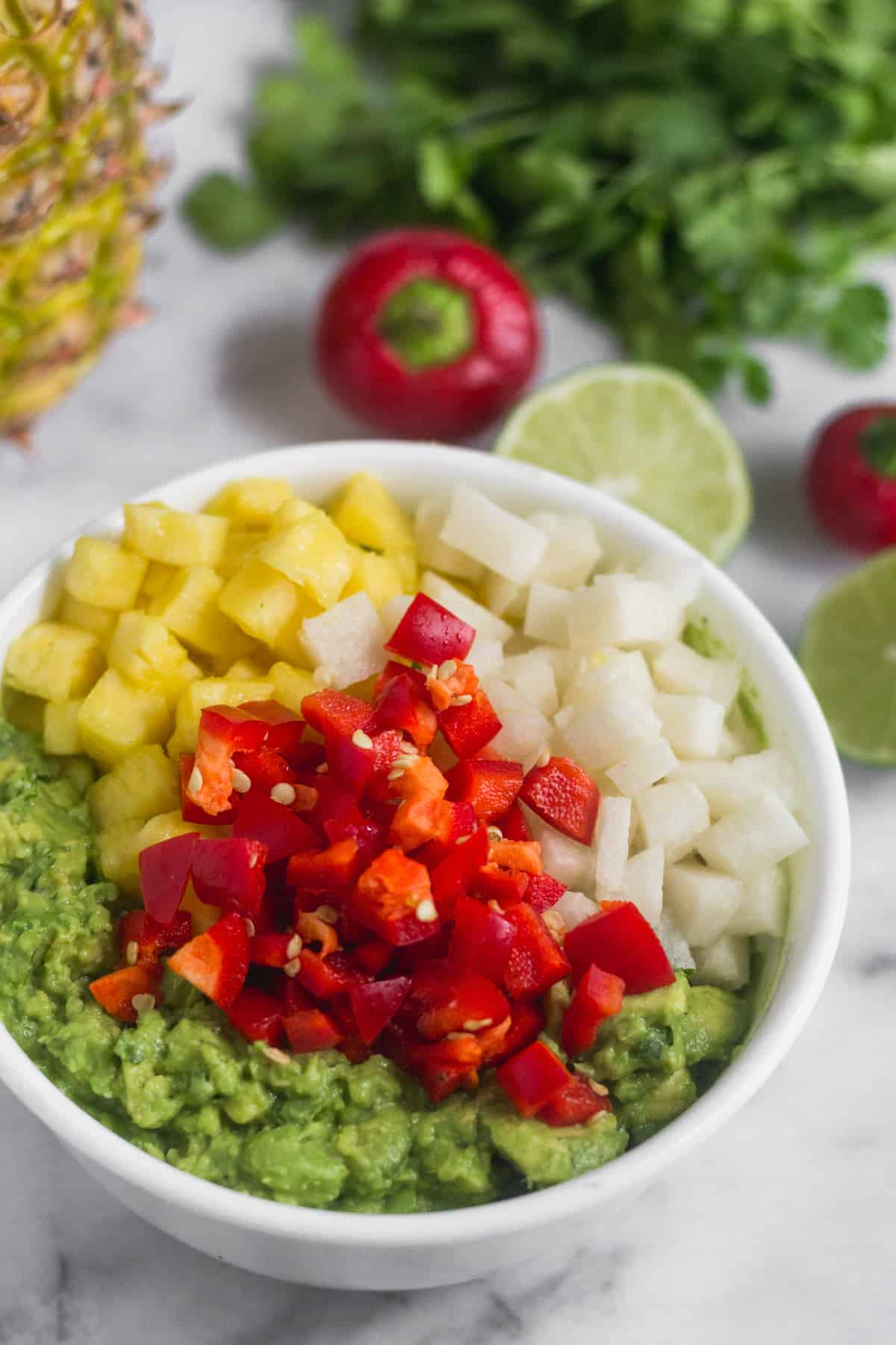 White bowl filled with mashed avocado, diced pineapple, diced jicama, and diced cherry peppers, with limes, cherry peppers, cilantro, and a pineapple behind it