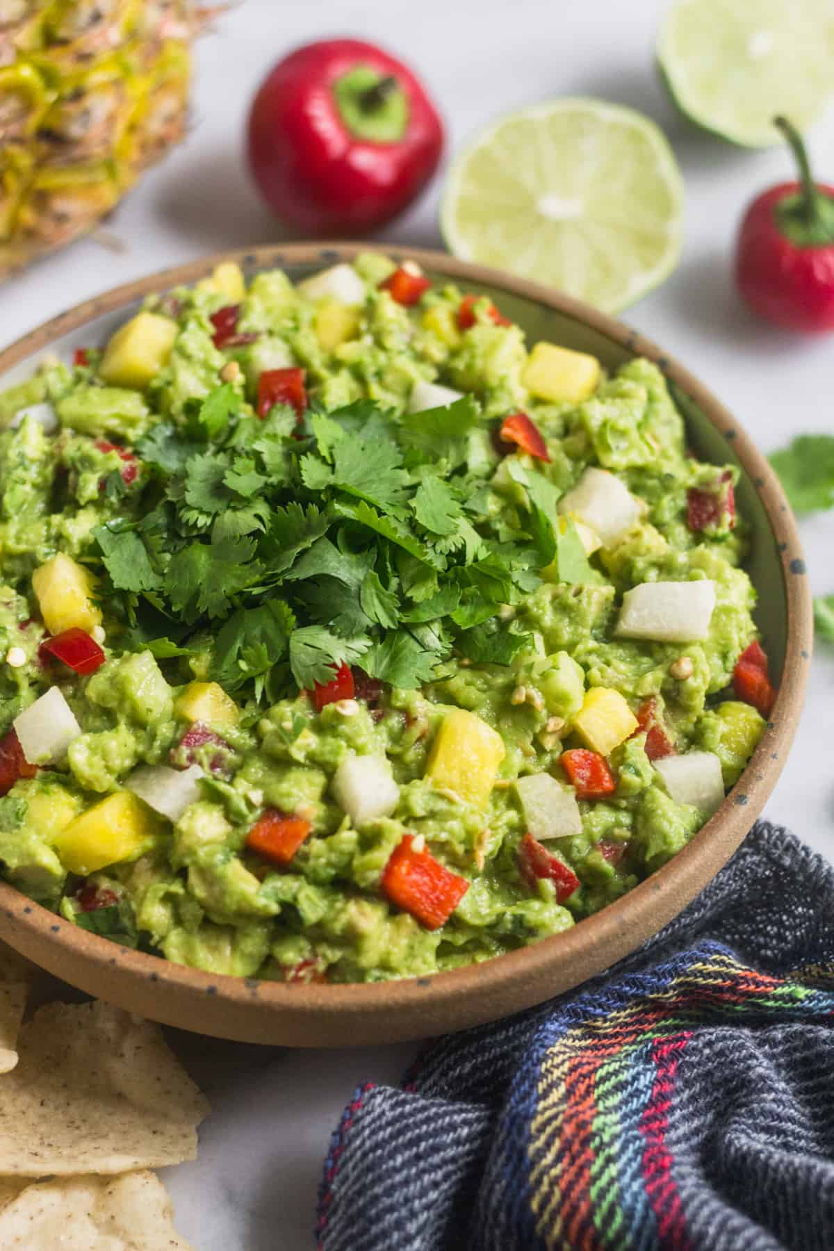 Large bowl filled with pineapple jicama guacamole with a blue towel, chips, limes, and cherry peppers around it