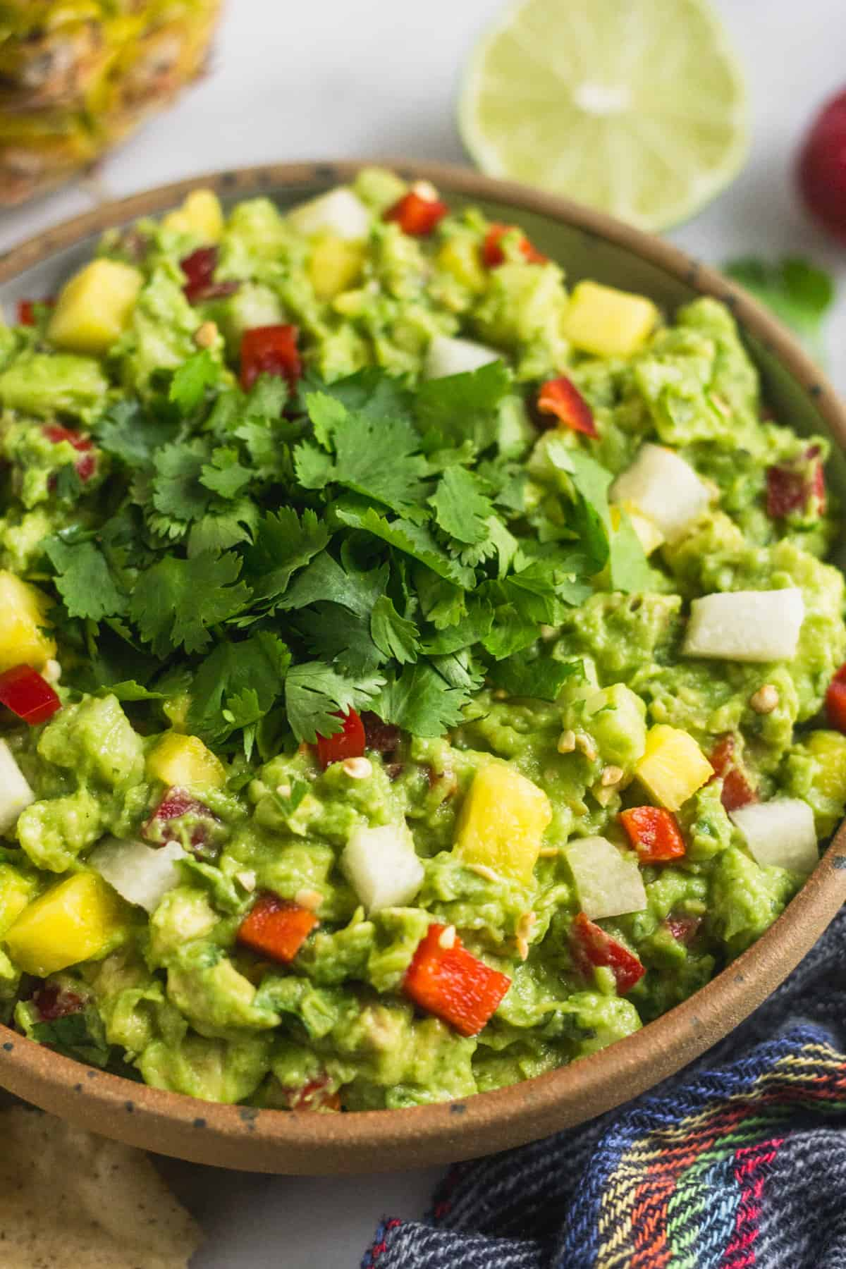 Close up of a bowl filed with spicy pineapple jicama guacamole topped with fresh cilantro