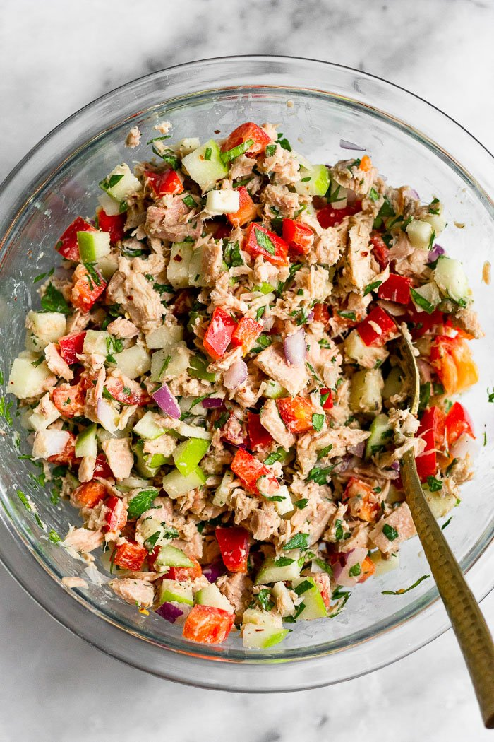 Tuna tahini apple salad in a large glass bowl with a spoon coming out of it.