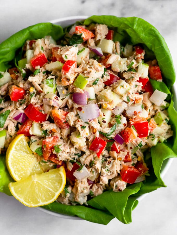 Overhead shot of whole30 tuna salad with apples, peppers, onion, and tahini. It is in lettuce cups in the bowl with lemon wedges as garnishes.