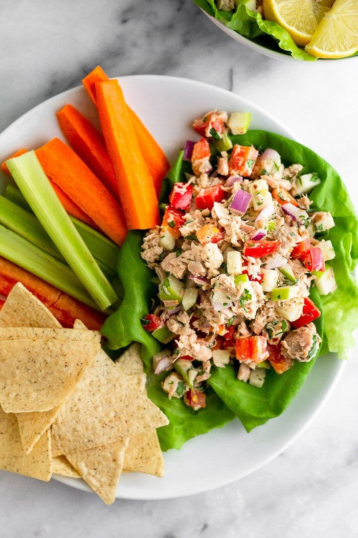 Paleo tuna salad on lettuce leaves with carrot and celery sticks and chips on a plate.