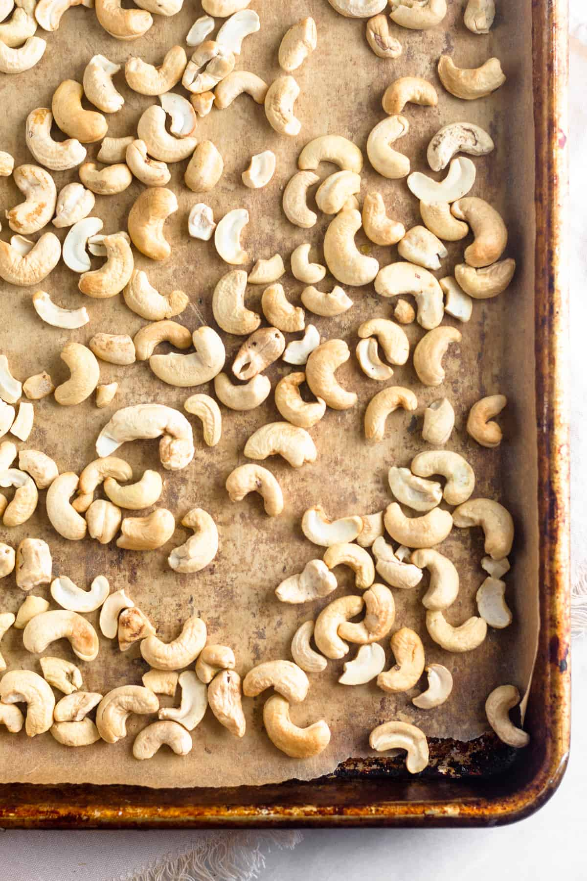 Baking sheet lined with parchment paper and full of roasted cashews