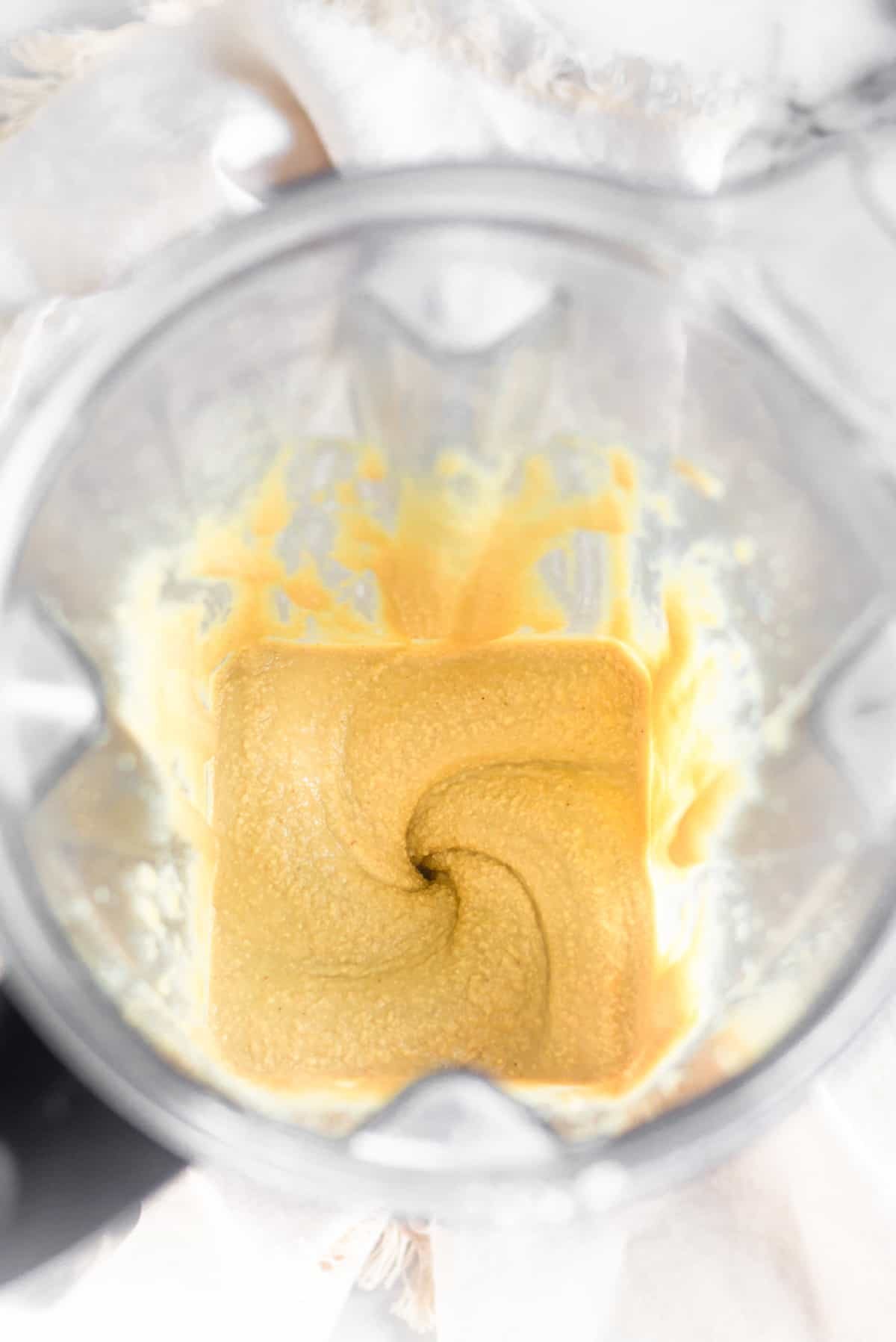 A blender filled with freshly blended cashew coconut butter