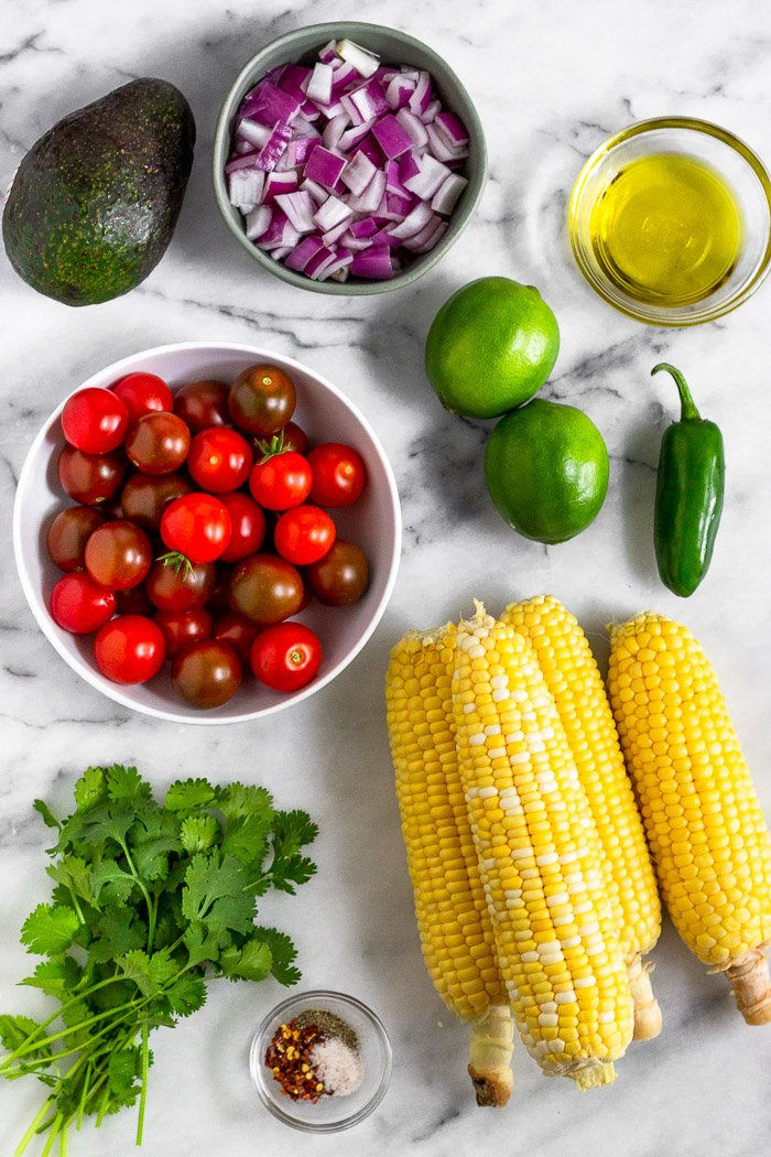 White counter top with an avocado, bowl of red onion, bowl of olive oil, limes, a jalapeño, 4 ears of corn. bunch of cilantro, and a bowl of cherry tomatoes.