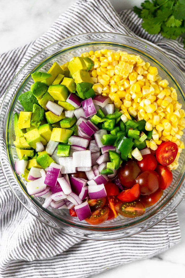 Glass bowl filled with corn that has been removed from the cob, chopped tomatoes, diced avocado, diced red onion. and diced jalapeños.