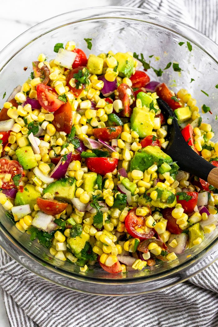 Large glass bowl filled with summer corn salad all mixed up with a wooden spoon sticking out of it.
