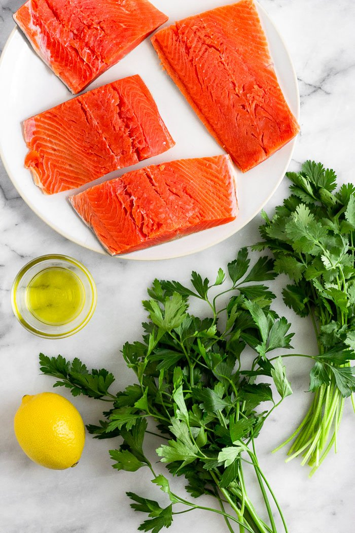 White counter with raw salmon filets on a plate, a bunch of parsley, a bunch of cilantro, a lemon, and a small bowl of olive oil.