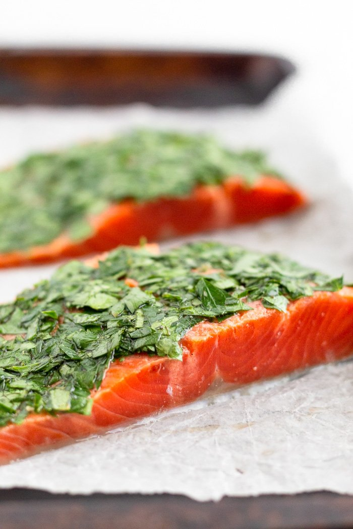 Raw salmon covered with fresh parsley, cilantro, lemon juice, and olive oil on a baking sheet.
