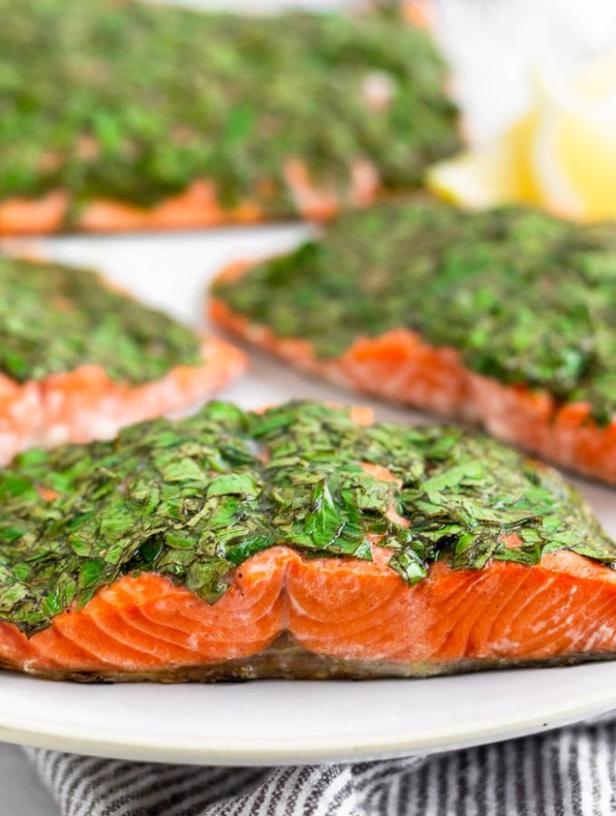 Plate filled with filets of herb grilled salmon and lemon wedges.