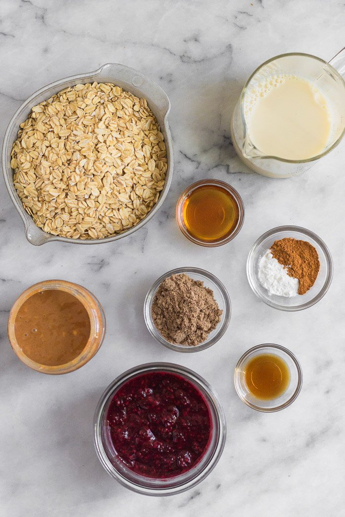 Overhead shot of different small bowls filled with rolled oats, almond milk, maple syrup, spices, ground flax, vanilla extract, peanut butter, and jelly.