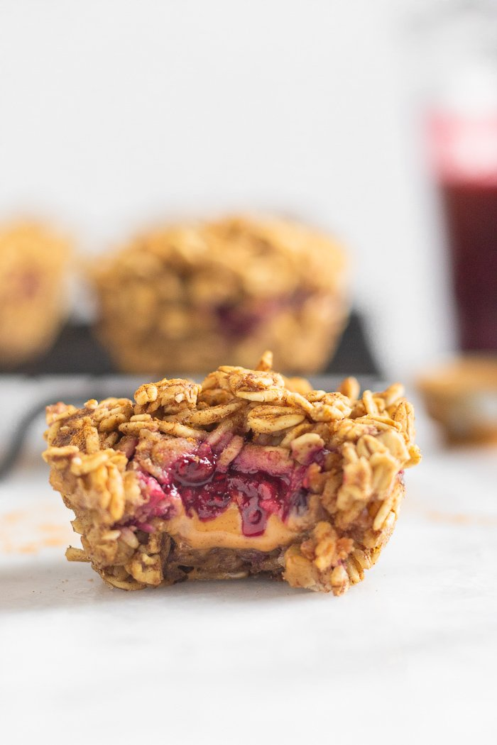Baked oatmeal cup with a bite taken out of it with peanut butter and jelly coming out. Behind it is a cooling rank with more muffins, a jar of jam, and a spoon of peanut butter.
