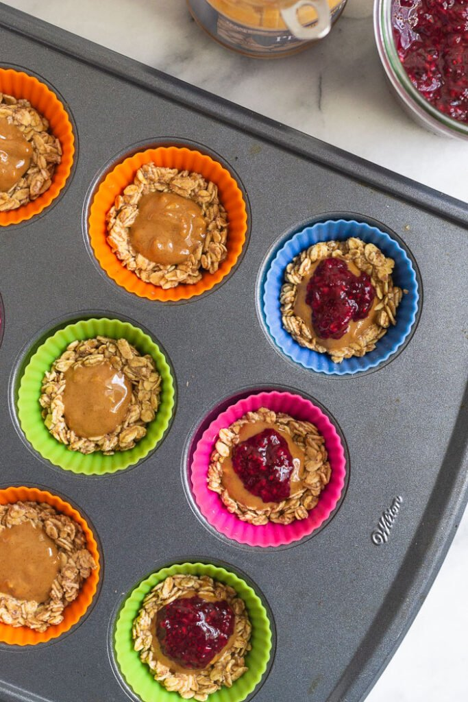 Overhead shot of silicon muffin liners filled with a rolled oat mixture and then layered with peanut butter and jelly.