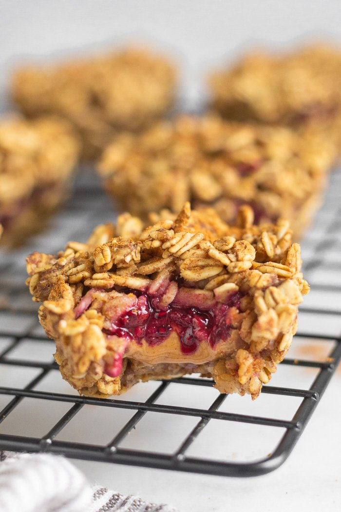 Peanut butter oatmeal muffins on a cooling rack. The closest one has a bite taken out of it with peanut butter and jelly in it.