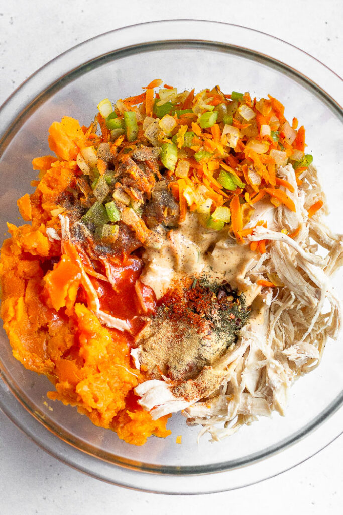 Large glass bowl filled with shredded chicken, mashed sweet potato, veggies, mayo, hot sauce, and spices.