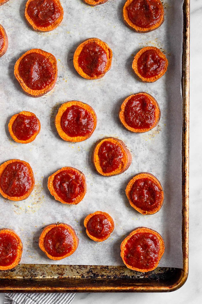 A baking sweet lined with parchment paper with cooked sweet potato rounds topped with sauce.