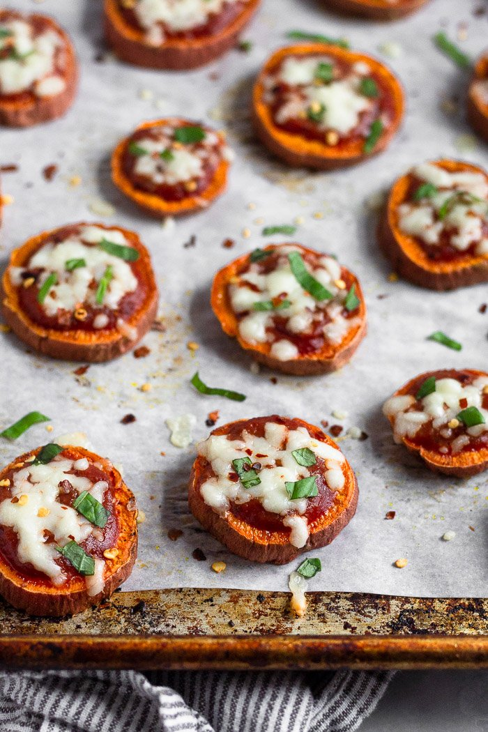 A lot of sweet potato pizza on a baking sheet. They are sprinkled with basil and red pepper flakes.