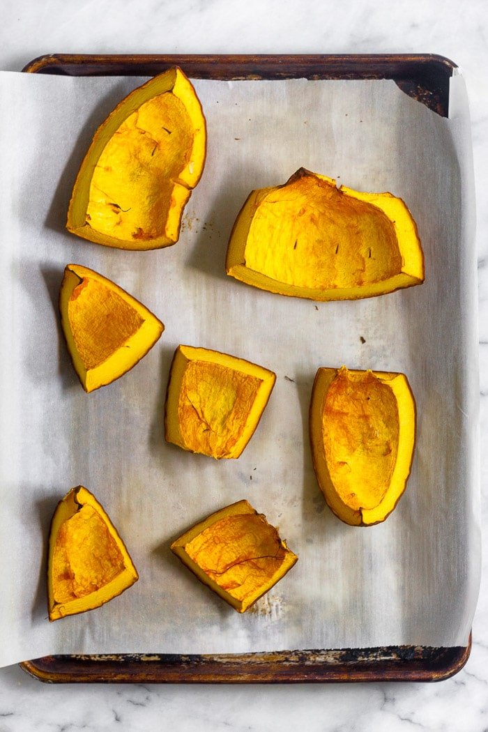 Baking sheet with big pieces of roasted pumpkin on it.