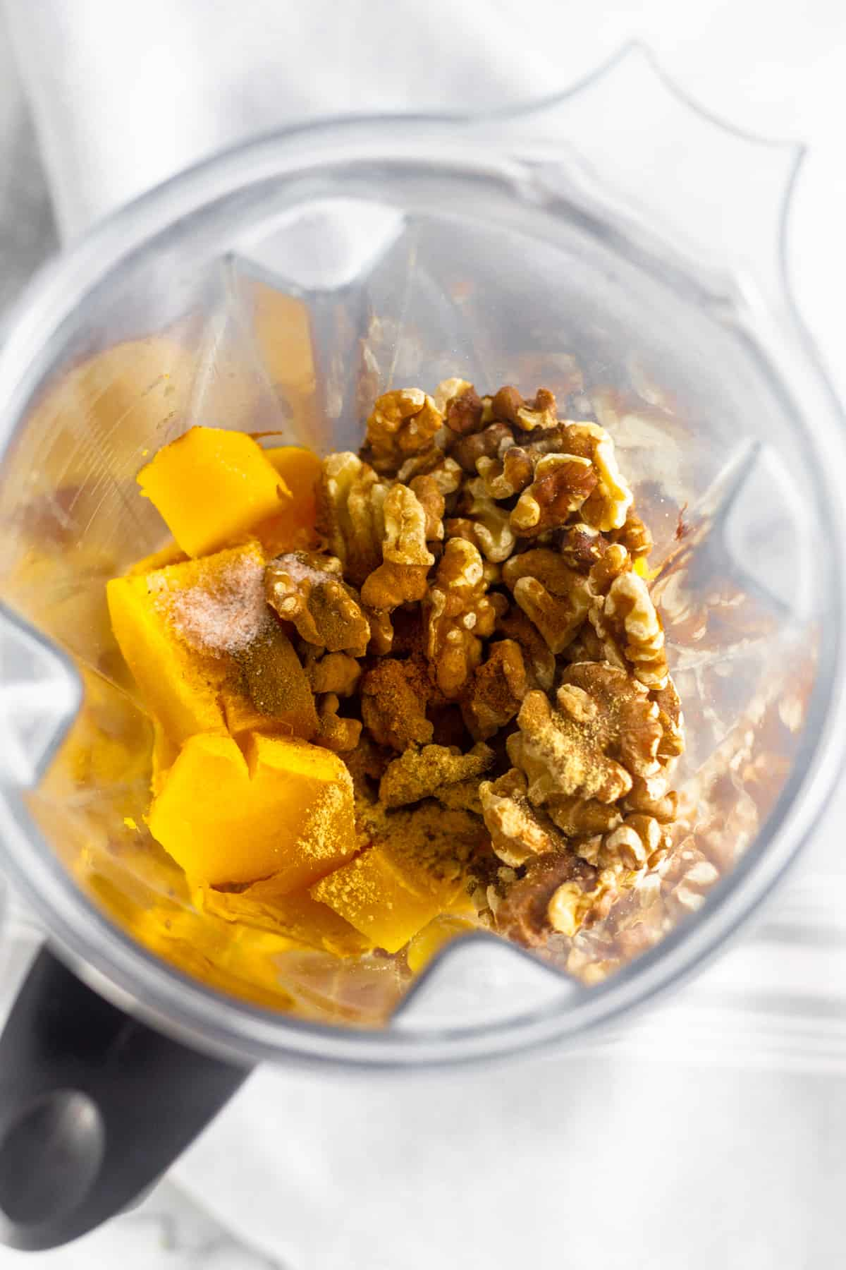 A blender filled with fresh pumpkin, toasted walnuts, and spices to make pumpkin pie butter