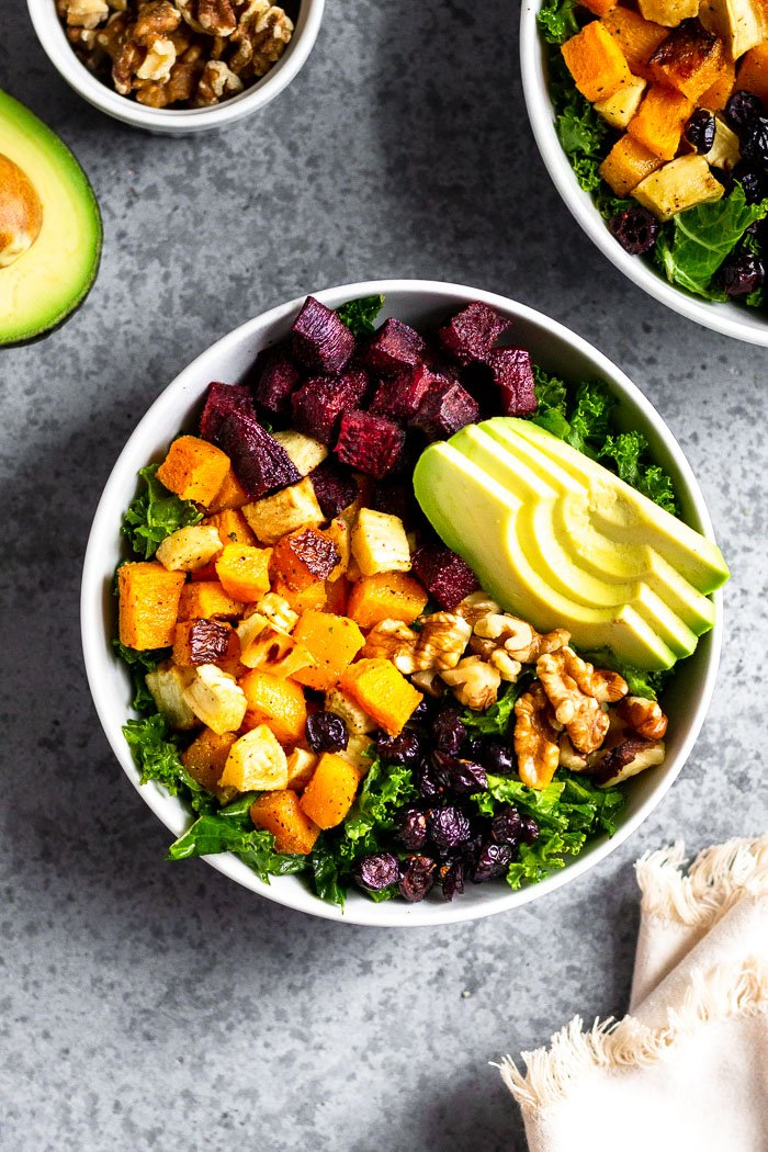 Butternut squash power bowl with kale, beets, parsnips, avocado, walnuts, and dried cranberries, all topped with a tahini dressing. Next to it is a kitchen towel, another bowl, container of walnuts, and half an avocado.