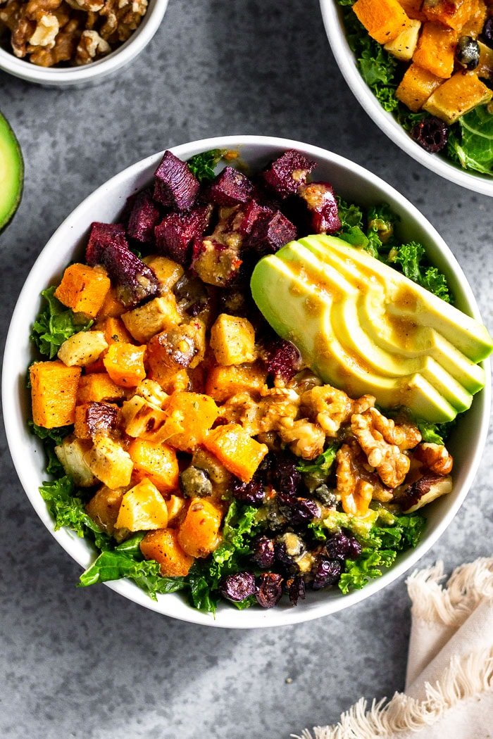 Veggie power bowl with kale, butternut squash, parsnips, beets, avocado, walnuts, and dried cranberries. It is topped with tahini dressing. Next to is is another bowl, half an avocado, bowl of walnuts, and a kitchen towel.